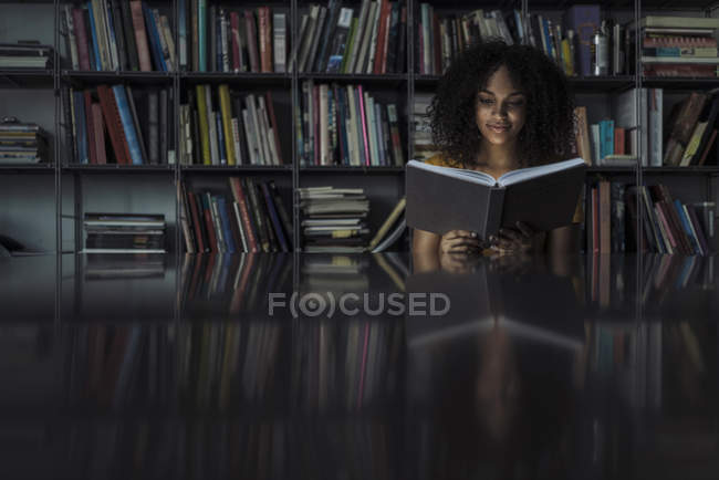 Jeune femme lecture livre dans la bibliothèque — Photo de stock