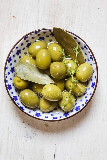 Оливки в миску с тимьяном и лавровый лист — стоковое фото