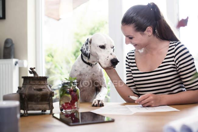 Усміхаючись молода жінка на столі Петтінг собака — стокове фото
