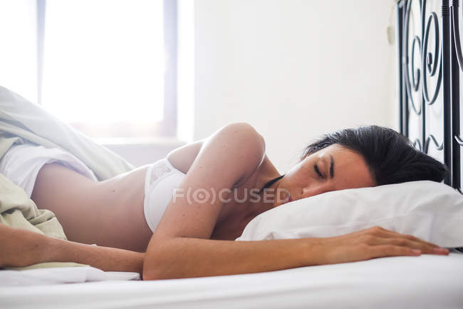 Young attractive woman in lingerie lying in bed, sleeping — Stock Photo