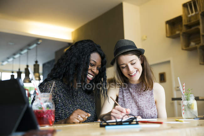 Two friends using digital tablet in cafe — Stock Photo