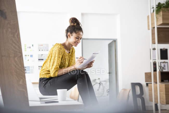 Femme souriante assise sur un bureau travaillant sur du papier — Photo de stock
