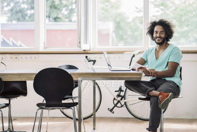 Joven diseñador sentado en la oficina usando el ordenador portátil - foto de stock