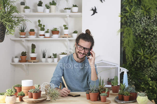 Young man with a collection of cacti on the phone — Stock Photo