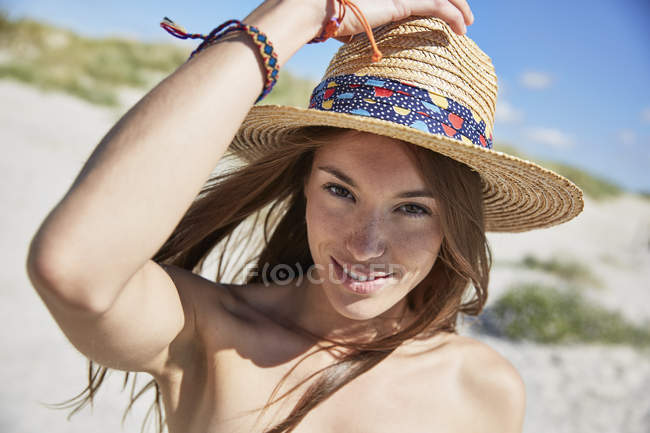 Улыбающаяся молодая женщина мерцает на пляже — стоковое фото