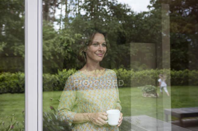 Femme souriante tenant la tasse et regardant par la fenêtre — Photo de stock