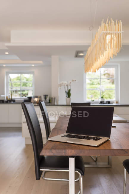 Modern dining area with open plan kitchen on background — Stock Photo