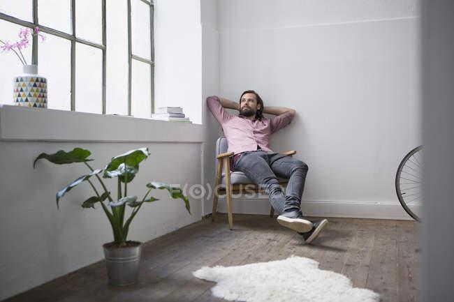 Uomo che si siede nella sedia e sognare ad occhi aperti a casa — Foto stock