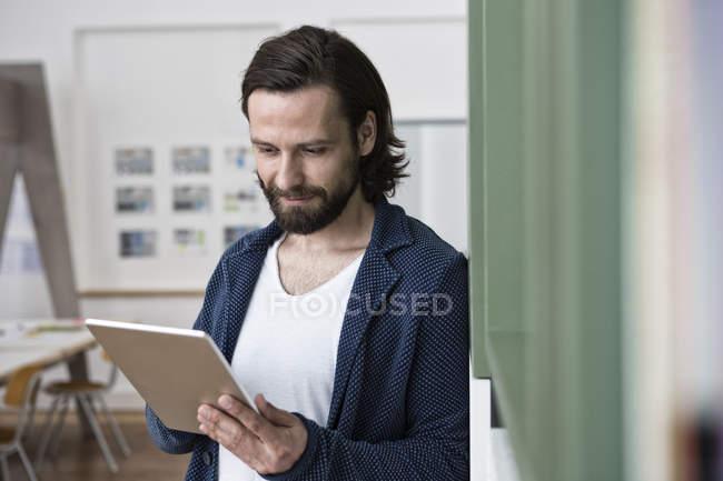 Homme utilisant une tablette numérique au bureau — Photo de stock