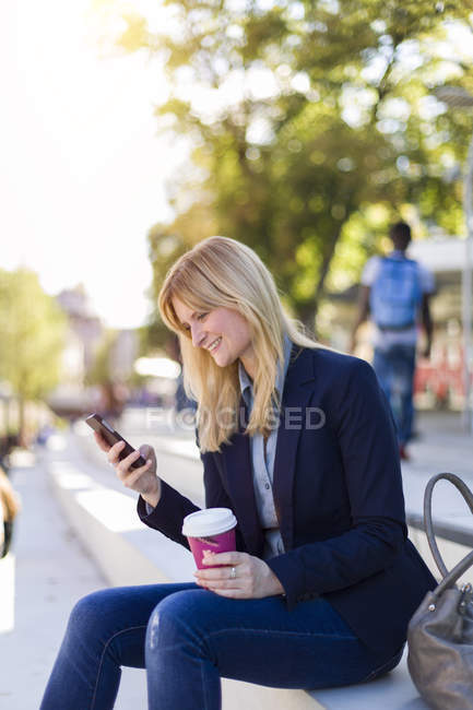 Smiling b businesswoman with coffee to go looking at smartphone — Stock Photo