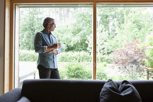 Uomo maturo che tiene la tazza guardando fuori dalla finestra — Foto stock
