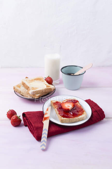 Toast with strawberry jam on plate served on table — Stock Photo