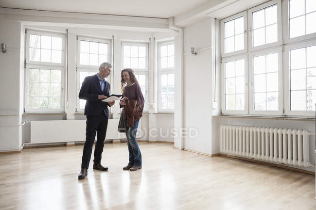 Real estate agent talking to client in empty apartment — Stock Photo