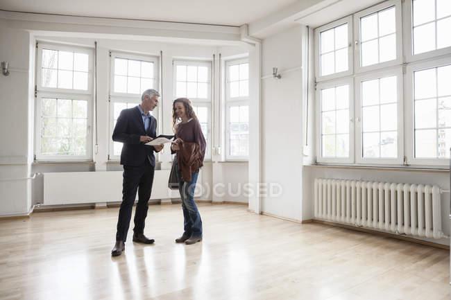 Agente immobiliare che comunica al client in appartamento vuoto — Foto stock