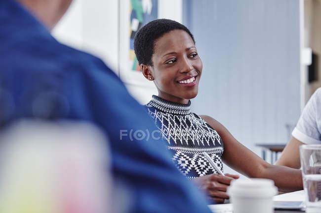 Улыбающаяся женщина на встрече в современном офисе — стоковое фото