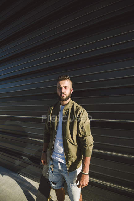 Man with skateboard standing in front of black facade — Stock Photo