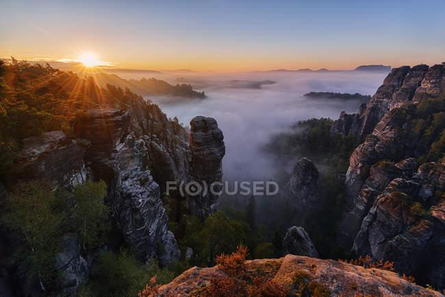 The rock needle Hllenhund and Raaber Kessel, sunrise (dawn) and fog, Saxon Switzerland National Park, Saxony, Germany, Europe — Stock Photo