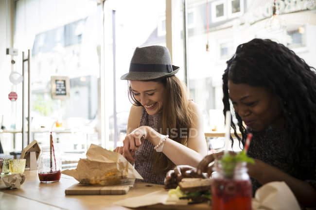Amigos sentados no café, comendo sanduíche — Fotografia de Stock