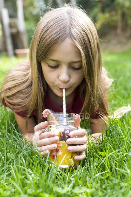 Дівчина лежав на луг і питної води пройняті різних фруктів — стокове фото