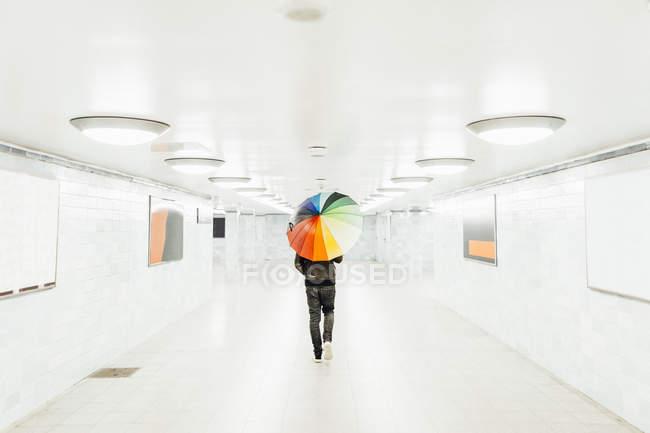 Mann mit buntem Regenschirm läuft durch leeren U-Bahn-Tunnel in Berlin — Stockfoto