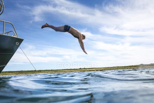 Croatia, Pula, senior man jumping from boat into water — Stock Photo