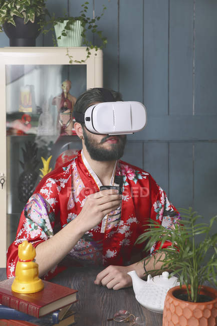 Portrait of young man having tea in virtual reality glasses — Stock Photo