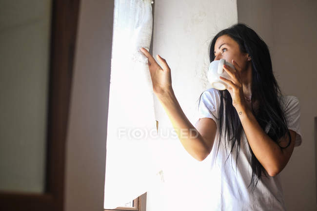 Young attractive woman drinking coffee at window — Stock Photo