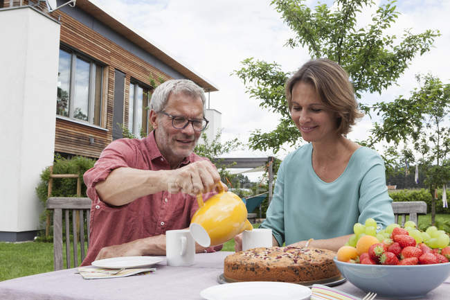 Mature couple in garden having afternoon break — Stock Photo
