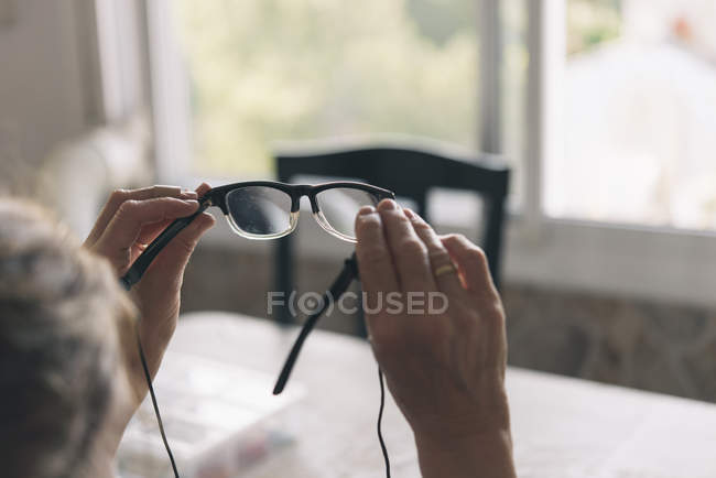 Mani di donna che tengono gli occhiali — Foto stock