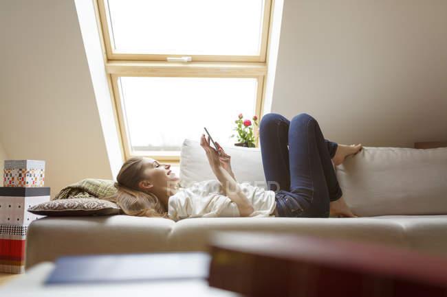Расслабленная женщина лежит на диване с помощью мобильного телефона — стоковое фото