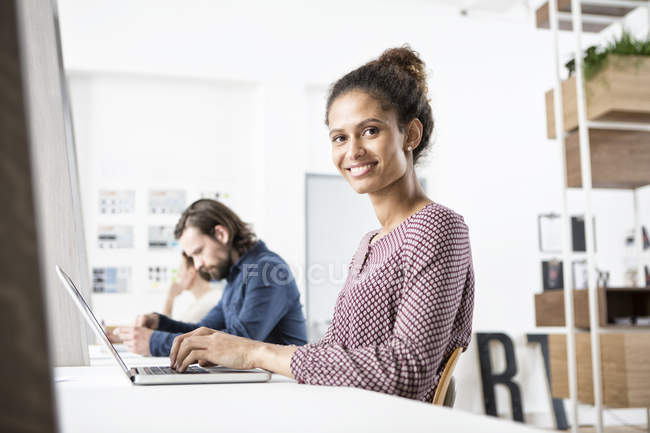 Smiling woman in office working on laptop — Stock Photo