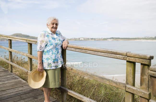 Happy senior woman standing on boardwalk — Stock Photo