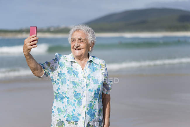 Smiling senior woman taking selfie on the beach — Stock Photo