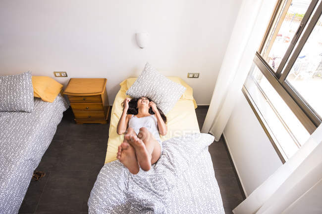 Overhead view of Teenage girl lying in the bed — Stock Photo