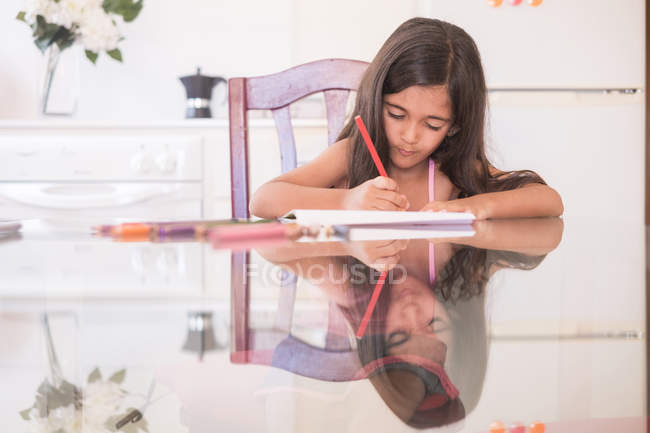 Young girl on the table doing home work — Stock Photo
