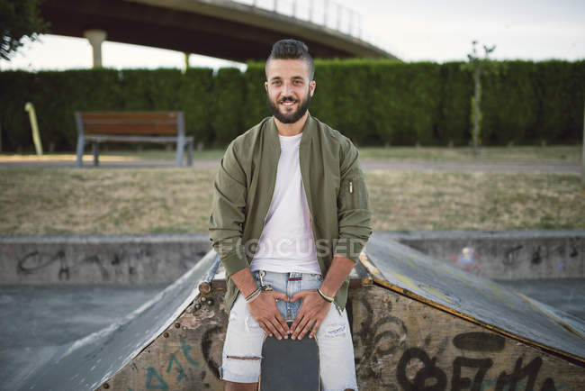 Smiling man with skateboard leaning on ramp in skatepark — Stock Photo