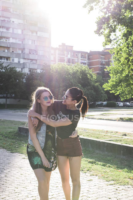 Two female friends standing on street at backlit — Stock Photo