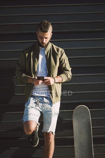 Homem com skate em pé na frente da fachada e usando telefone celular — Fotografia de Stock