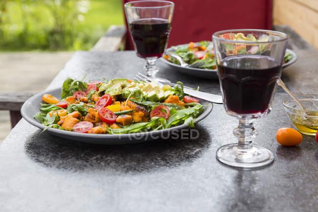 Salada e copos de vinho tinto — Fotografia de Stock