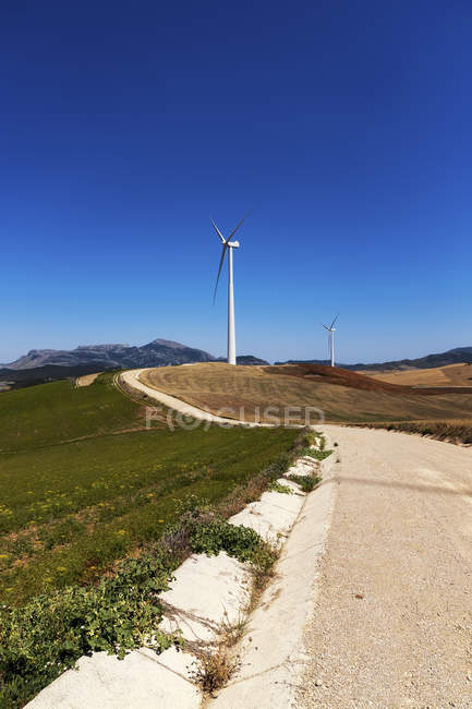 Spain, Andalusia, Wind turbines, country road and fields view — Stock Photo