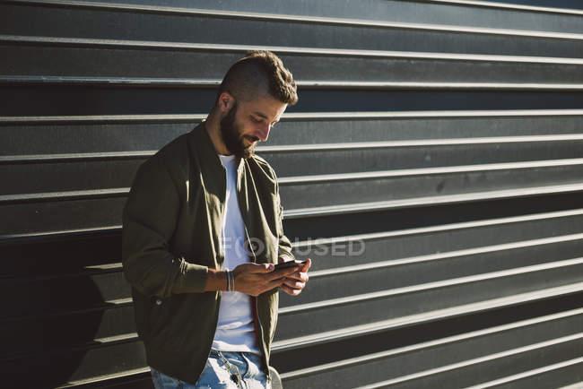 Lächelnder Mann steht vor Fassade und benutzt Handy — Stockfoto