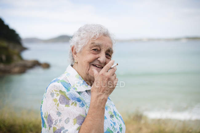 Portrait of smiling senior woman with cigarette — Stock Photo