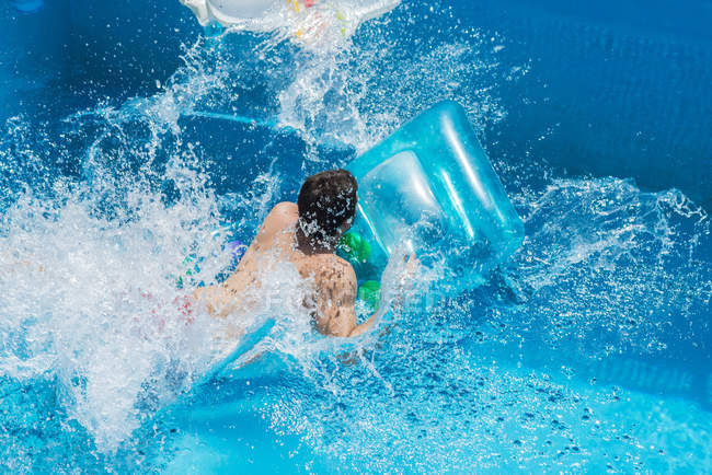 Man in the pool on airbed, moving, water splashes — Stock Photo