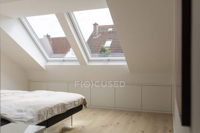 Windows in modern bedroom of penthouse with wooden floor — Stock Photo