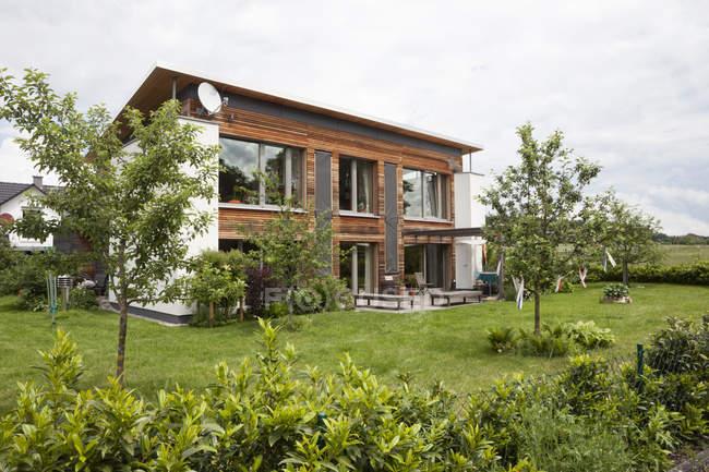 Vista diurna de una casa residencial moderna con jardín - foto de stock