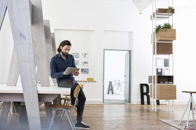 Homme assis sur le bureau en utilisant une tablette numérique — Photo de stock