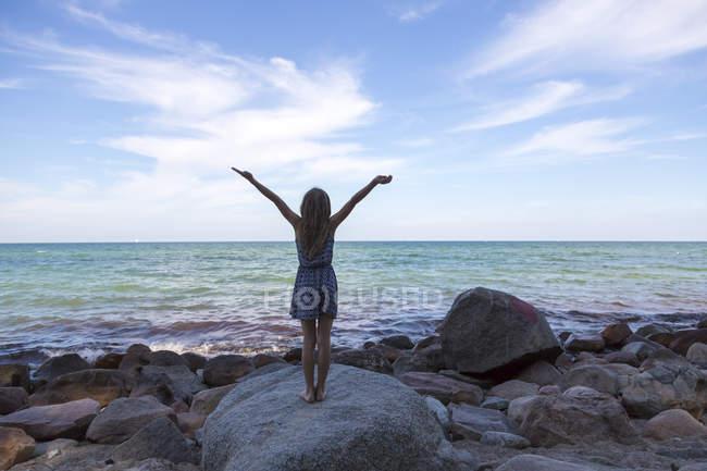Fille avec les bras levés debout sur le rocher et regardant la mer — Photo de stock