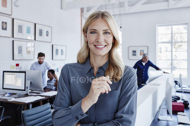 Portrait of smiling businesswoman in office with staff in background — Stock Photo
