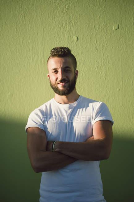 Ritratto di uomo sorridente con le braccia incrociate in piedi davanti a sfondo verde — Foto stock