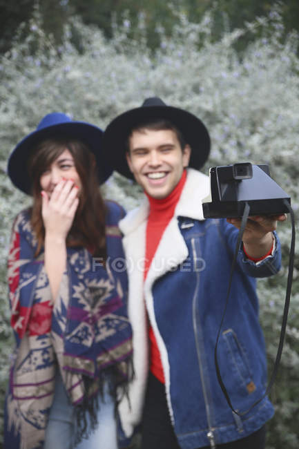 Happy young couple taking photo with retro camera — Stock Photo